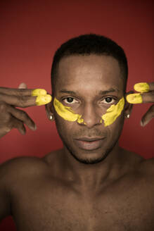 Headshot of adult African American man with yellow smears of paint on face looking at camera - ADSF00139