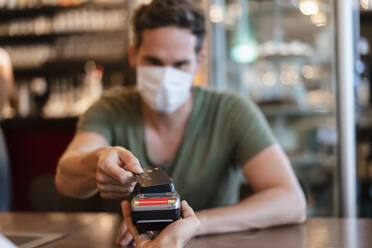 Man with protective mask paying with credit card in restaurant - DIGF12747