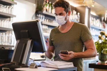 Restaurant manager with protective mask using computer and smartphone - DIGF12753