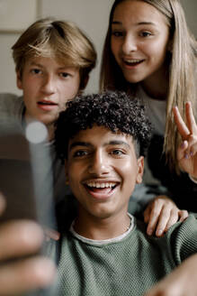 Smiling teenage boy taking selfie with friends through mobile phone at home - MASF18680