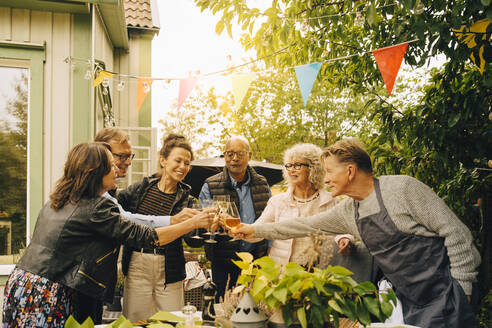 Active senior male and female friends with celebratory toast at back yard during garden dinner party - MASF19012