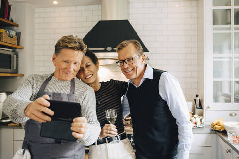Smiling man taking selfie with friends standing in kitchen at home - MASF19015