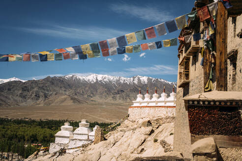 Wall of Buddhist temple and colorful prayer flags against blue sky and mountains with snow covered peaks in sunny day in Ladakh in India - EHF00471