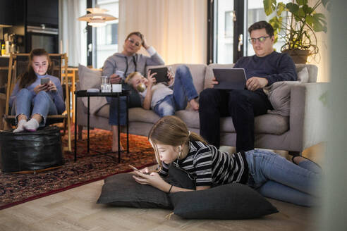 Family is using technologies in living room at modern home - MASF19427