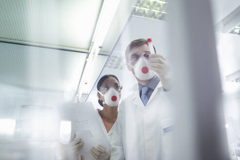 Scientists in isolation environment wearing masks, working in research laboratory. - CUF55673