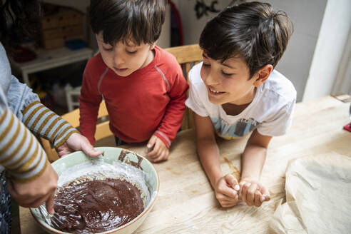 Two boys with black hair sitting at a kitchen table, baking chocolate cake. - CUF55685