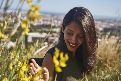 Portrait of smiling young woman with long brown hair standing on hill above city. - CUF55754