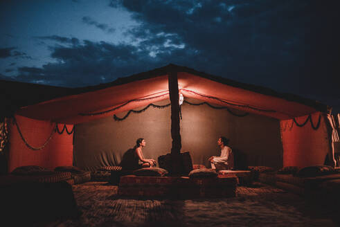 Side view of young man and woman sitting in big tent lit by lamp in darkness of night - ADSF00206