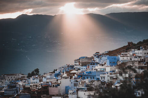 Buildings of Morocco spread over hill and lit by bright sunbeams through overcast sky on background of majestic high mountain - ADSF00209