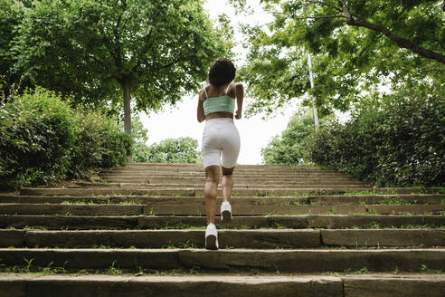 Rear view of female jogger on steps - XLGF00337