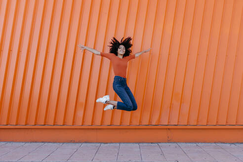 Happy young woman jumping with arms outstretched against orange wall - TCEF00914