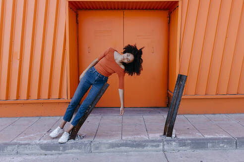 Young woman with afro hairstyle leaning on damaged metal against orange door - TCEF00917