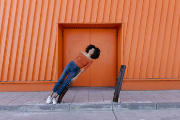 Afro woman leaning on metal against orange door - TCEF00920