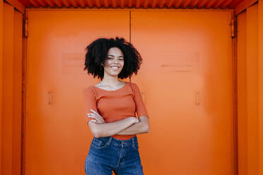Smiling young afro woman standing with arms crossed against orange door - TCEF00923