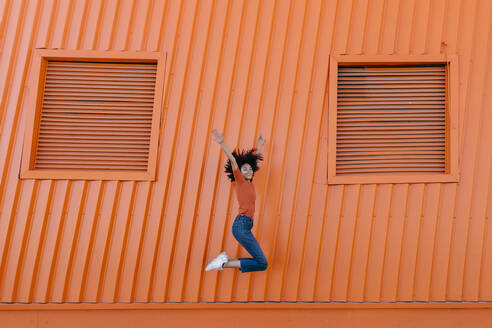 Happy young woman jumping with arms raised against orange wall - TCEF00926