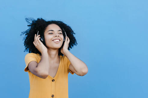 Young afro woman enjoying while listening music through headphones against blue wall - TCEF00932