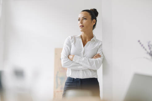 Thoughtful businesswoman with arms crossed standing by wall in home office - JOSEF01283