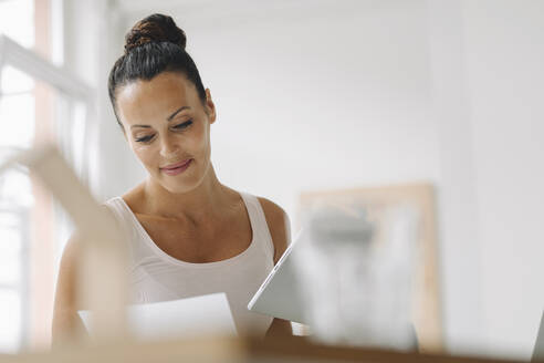 Smiling woman holding digital tablet reading document while sitting at home office - JOSEF01325