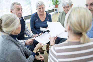 Group of seniors attending therapy group in retirement home, using sheets of paper - WESTF24608