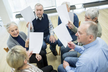 Group of seniors attending therapy group in retirement home, using sheets of paper - WESTF24611