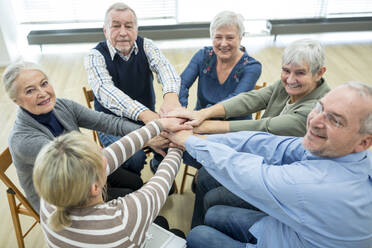 Group of active seniors stacking hands, symbolizing solidarity - WESTF24614