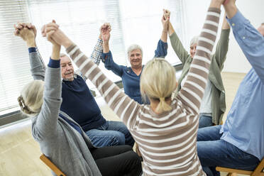 Group of seniors practicing chair gymnastics with instructor  in retirement home - WESTF24623