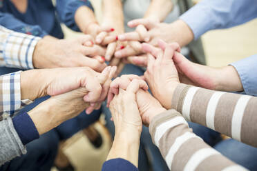 Close up of seniors, stacking hands, symbolizing solidarity - WESTF24626