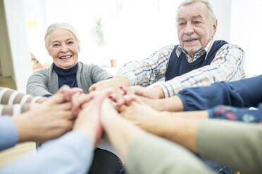 Group of active seniors stacking hands, symbolizing solidarity - WESTF24629