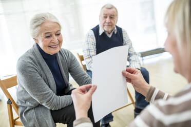 Senior woman in therapy goup on retiremnet home reading sheet of paper - WESTF24632