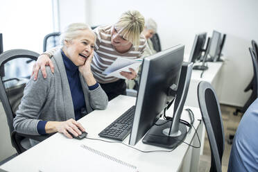 Active seniors attending computer course, intructor giving advice - WESTF24650