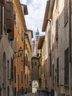 Italy, Province of Cremona, Cremona, Old empty alley with towers of Cremona Cathedral in background - MCVF00499