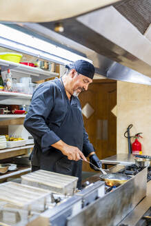 Chef with pan in traditional Spanish restaurant kitchen - DLTSF00831