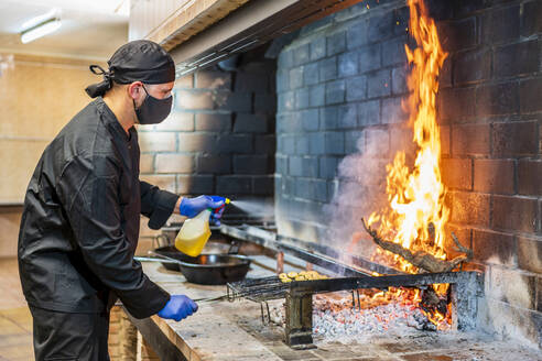 Traditional cooking of paella in restaurant kitchen, chef wearing protective mask - DLTSF00846