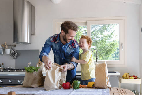 Cheerful father and son with groceries standing at dining table in kitchen - EIF00015