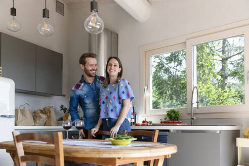 Smiling woman with man standing in kitchen at home - EIF00030