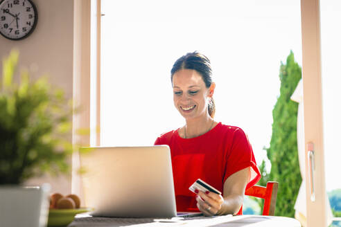 Smiling beautiful woman holding credit card while using laptop at dining table against window - EIF00051