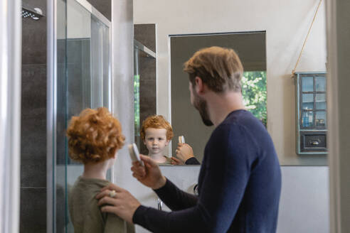Cute boy looking at mirror reflection of father brushing his hair in bathroom - EIF00057