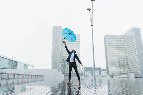 African-American male in business clothes trying to catch blue umbrella flying up on gust of wind and looking up standing on wet after rain pavement on background of grey city buildings - ADSF00510