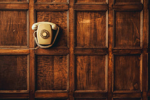 Composition of vintage phone hanging on wooden ornamented wall - ADSF00618