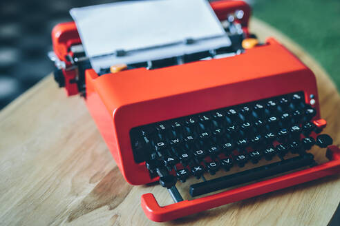 Close-up bright red typewriter on small table with paper sheet inserted - ADSF00627