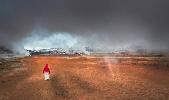 Back view of anonymous person walking in amazing valleys near majestic geysers in Iceland - ADSF00882
