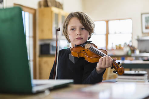 Six year old boy playing violin, having a remote video lesson in lockdown at home. - MINF14613