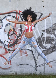 Young woman jumping in front of wall with graffiti - PGCF00078
