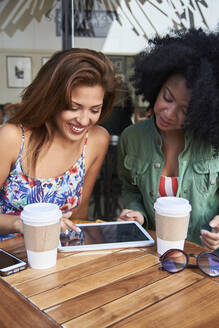 Girlfriends with coffee to go using tablet in cafe - PGCF00090