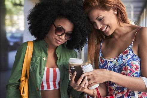 Girlfriends with coffee to go using smartphone - PGCF00093
