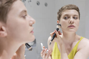 Short haired woman applying make-up with brush while looking at her reflection on mirror in bathroom - TAMF02488
