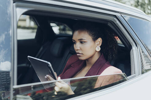 Young businesswoman using digital tablet seen through car window - MTBF00556
