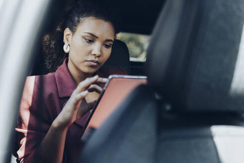 Young businesswoman using digital tablet while sitting in car - MTBF00559