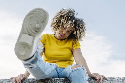 Young woman sitting on wall, showing sole of shoe - XLGF00360