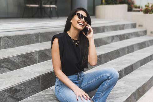 Woman with sunglasses using smartphone in city - DSIF00021